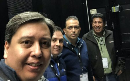 Four men posing in a datacentre